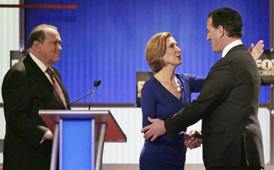 Photo - Republican presidential candidate, businesswoman Carly Fiorina speaks with Republican presidential candidate, former Pennsylvania Sen. Rick Santorum, right, as Republican presidential candidate, former Arkansas Gov. Mike Huckabee looks on after the Fox Business Network Republican presidential debate at the North Charleston Coliseum, Thursday, Jan. 14, 2016, in North Charleston, S.C. (AP Photo/Chuck Burton)