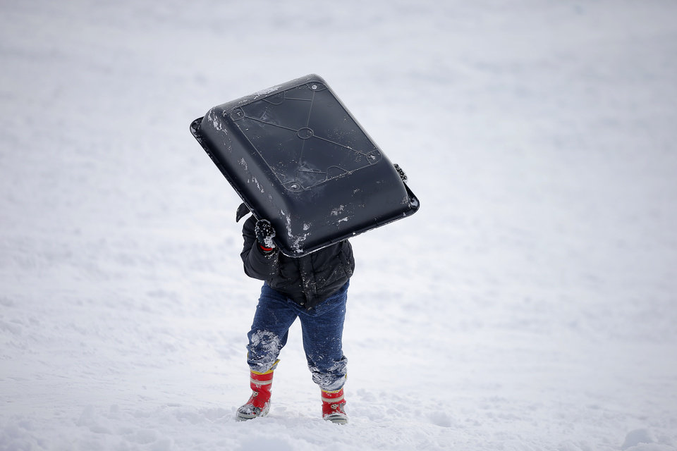 Photo - A child carries a sled back up a hill along W Hefner Road in Oklahoma City after a winter storm dropped another layer of snow in Oklahoma City, Wednesday, Feb. 17, 2021. [Bryan Terry/The Oklahoman]