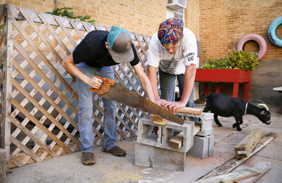 Photo -  Bruce Butler, 17, left, and Kenneth Curry, 16, both of Comanche, saw wood while building a platform for goat food storage in the garden area at FAME Academy. The school has two pygmy goats, Lucy, in background, and Ricky, not shown. [Photo by Nate Billings, The Oklahoman]