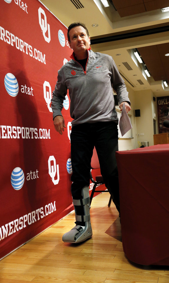 Photo - NATIONAL SIGNING DAY / SIGN / SIGNED / LETTER-OF-INTENT SIGNING DAY: University of Oklahoma head football coach Bob Stoops is seen wearing a protective boot following toe surgery as he leaves a press conference on National Signing Day at OU on Wednesday, Feb. 6, 2013, in Norman, Okla.  Photo by Steve Sisney, The Oklahoman