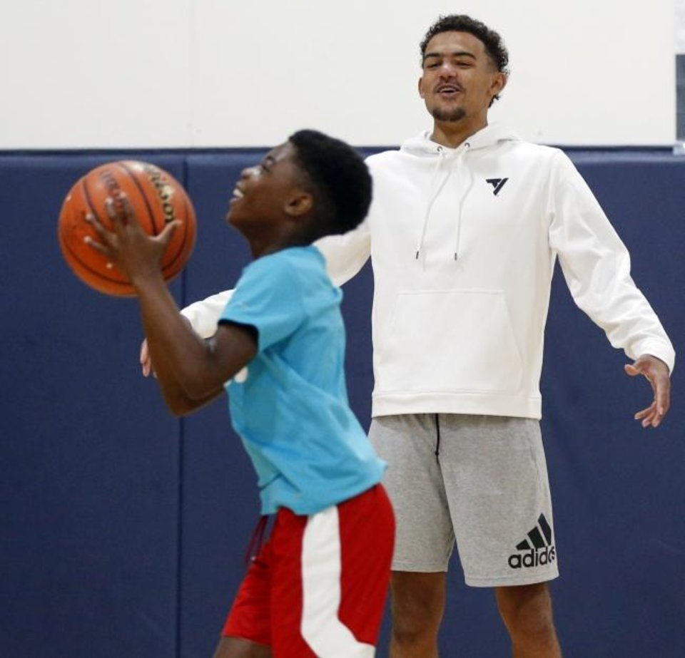 Photo -  Atlanta guard Trae Young talks to a participant taking a shot during his youth basketball camp at the Santa Fe Family Life Center in Oklahoma City on Saturday. [Nate Billings/The Oklahoman]