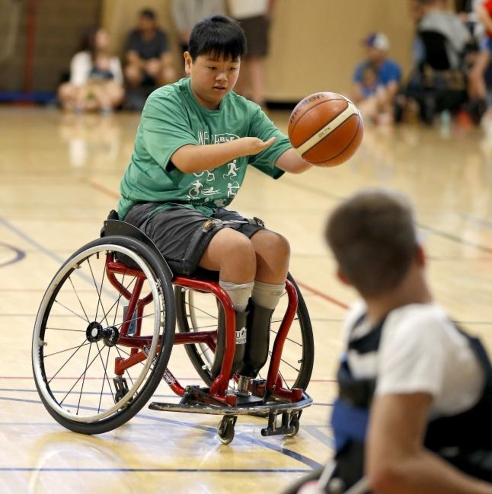 Photo -  Zion Redington, a 13-year-old from Tennessee, plays wheelchair basketball during the Endeavor Games at UCO Wellness Center in Edmond on Friday. [Bryan Terry/The Oklahoman]