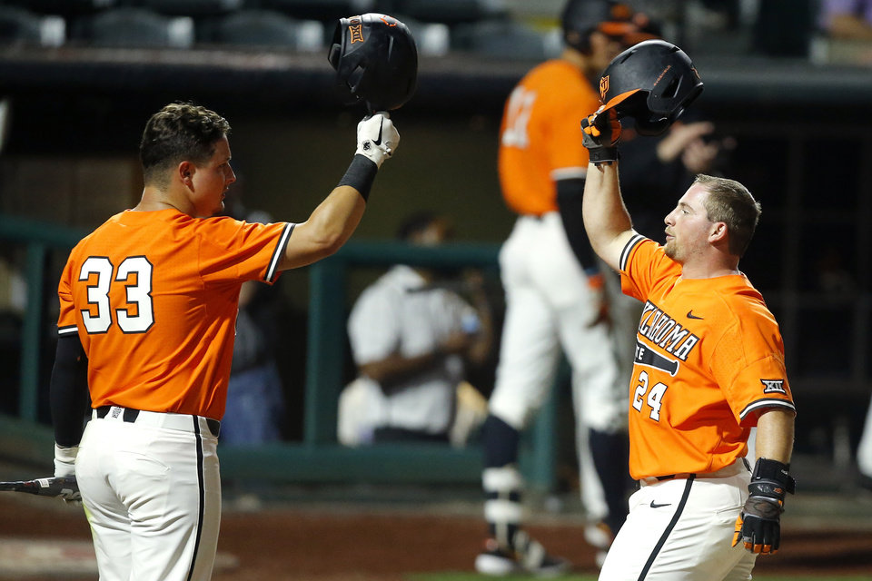 Photo - Oklahoma State's Colin Simpson (24) celebrates with Trevor Boone (33) after hitting a home run in the second inning of  a Big 12 baseball tournament game between Oklahoma State University (OSU) and TCU at Chickasaw Bricktown Ballpark in Oklahoma City, Okla., Wednesday, May 22, 2019.  [Bryan Terry/The Oklahoman]