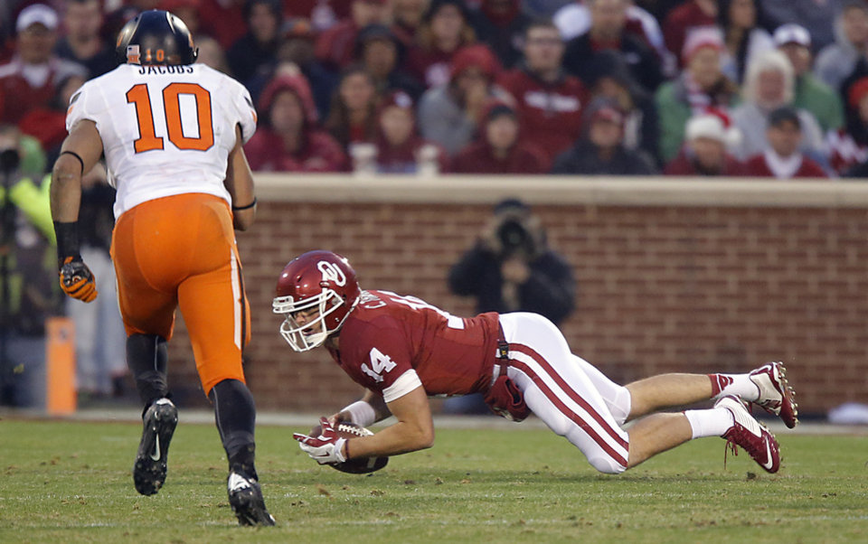Photo - Oklahoma's Cody Thomas (14) falls on a loose ball in front of Oklahoma State's Seth Jacobs (10) during a Bedlam college football game between the University of Oklahoma Sooners (OU) and the Oklahoma State University Cowboys (OSU) at the Gaylord Family Oklahoma Memorial Stadium in Norman, Okla. on Saturday, Dec. 6, 2014. Photo by Chris Landsberger, The Oklahoman