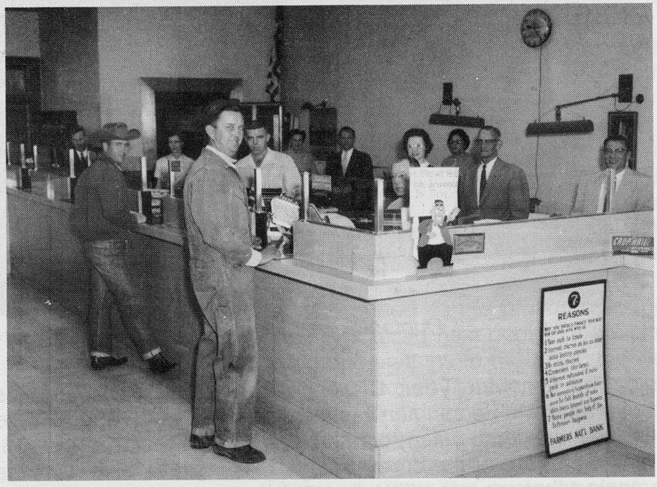 Photo -  B. Don Johnson, black suit and tie, foreground, Stancel Johnson, gray suit and tie, second from the right, and Bob Johnson, far right, are shown with customers at Farmers Bank in this 1950s era photo. Farmers Bank is now under the leadership of Aaron Johnson, great grandson of Stancel Johnson. [Photo provided]