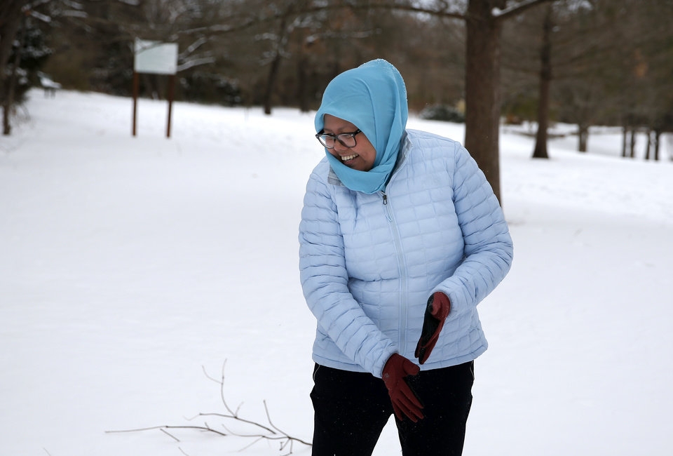 Photo - Jaja Naam laughs as she looks at her snow angle at Hafer Park in Edmond, Okla., Tuesday, Feb. 16, 2021. [Sarah Phipps/The Oklahoman]