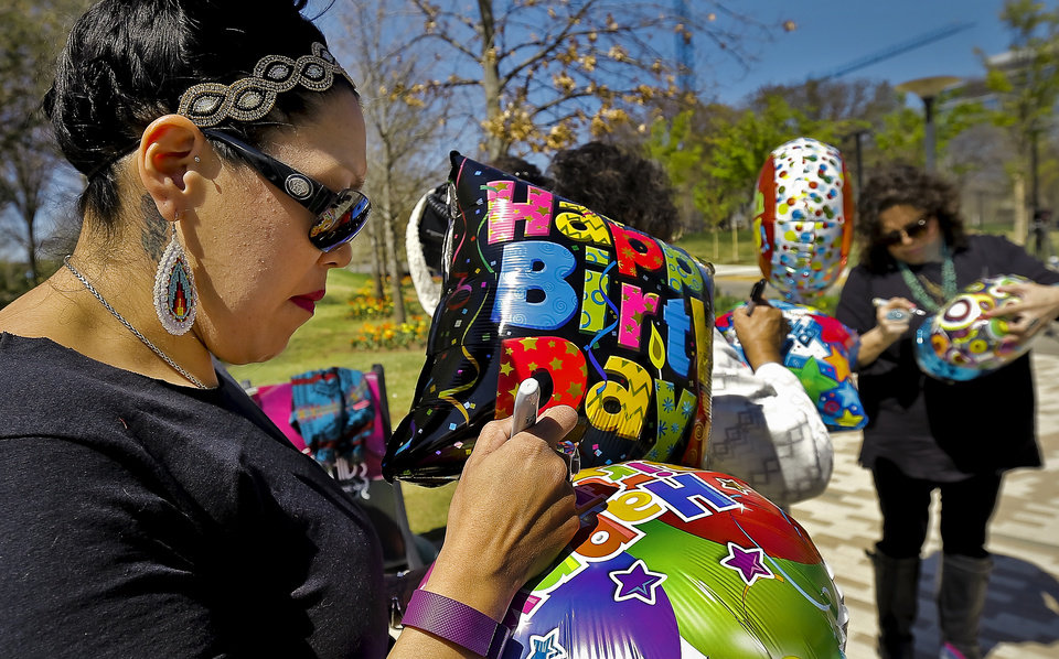 Photo - Melissa Wahnee writes a message on a balloon as she prepares to release the balloon in honor of her brother Bradley Wahnee, who was killed in 2009 during a drive by shooting, to mark his birthday at the Myriad Botanical Gardens in Oklahoma City, Okla. on Monday, March 21, 2016. The family releases balloons every year on Bradley's birthday and the date he was killed.  Photo by Chris Landsberger, The Oklahoman
