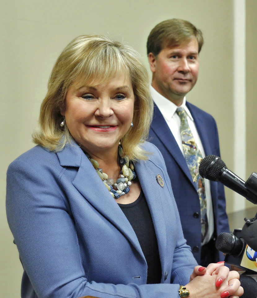 Photo - Gov. Mary Fallin has a broad smile when she gets the opportunity to answer questions from reporters about a new business coming to the state. Behind the governor is Steve Fendley,  president of Kratos Unmanned Systems Division. US Congressman Steve Russell joined Gov. Mary Fallin at the state Capitol on Friday, Jan. 26, 2018, to announce a company that produces high performance, jet-powered unmanned aerial tactical and target drone systems will open an office in Oklahoma. The state officials, including Vince Howie, aerospace and defense director for Oklahoma, Kratos Defense and Security Solutions, Inc. plans to open administrative and engineering offices and production facilities in Oklahoma City. Photo by Jim Beckel, The Oklahoman