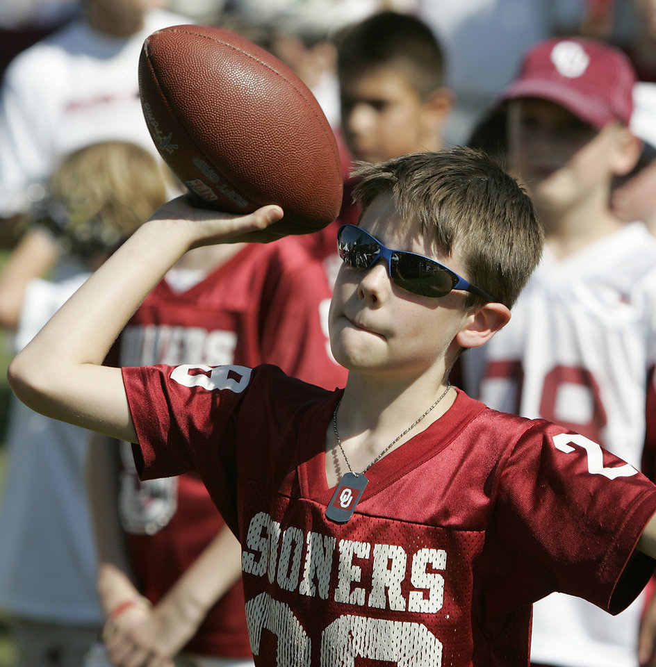 Photo - 9yr-old Jordan Gedosh of Norman throws the football before the start of the Oklahoma North Texas game at the Gaylord Family - Oklahoma Memorial Stadium, on Saturday, Sept. 1, 2007, in Norman, Okla. By STEVE GOOCH, The Oklahoman