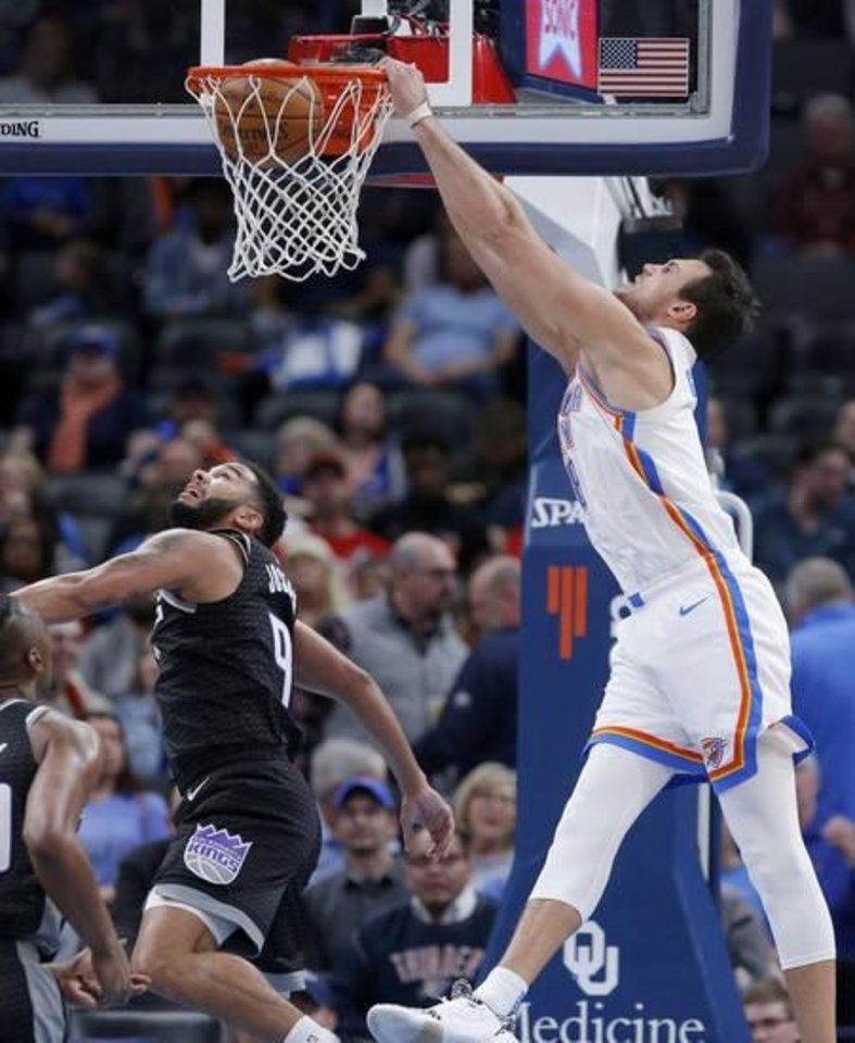 Photo -  Oklahoma City's Danilo Gallinari, right, slams home a dunk over Sacramento's Cory Joseph during Thursday night's game at Chesapeake Energy Arena. Gallinari scored a team-high 24 points to help OKC come back to beat the Kings 112-108. [Sarah Phipps/The Oklahoman]