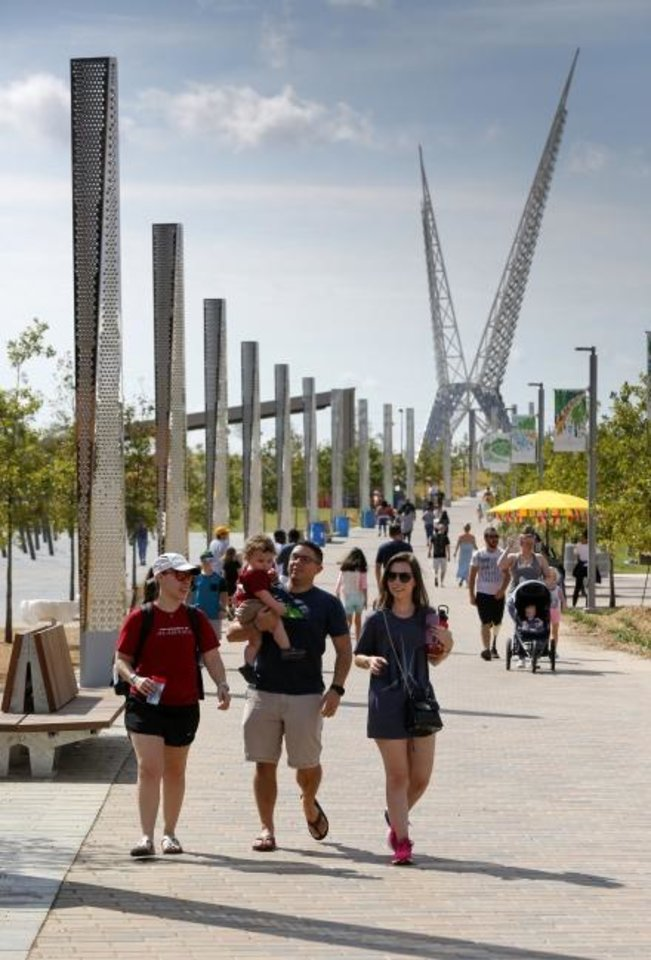 Photo -  People walk through the park with the Skydance bridge in the background during the grand opening weekend of Scissortail Park in Oklahoma City, Saturday, Sept. 28, 2019. [Nate Billings/The Oklahoman]