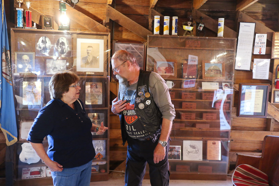 Photo -  Petra Hebert, from Prague, Oklahoma, and is of Czech descent, speaks with Frantisek Hrubacek, who is with a group of tourists from the Czech Republic, at the Round Barn. [Photo by Doug Hoke, The Oklahoman]