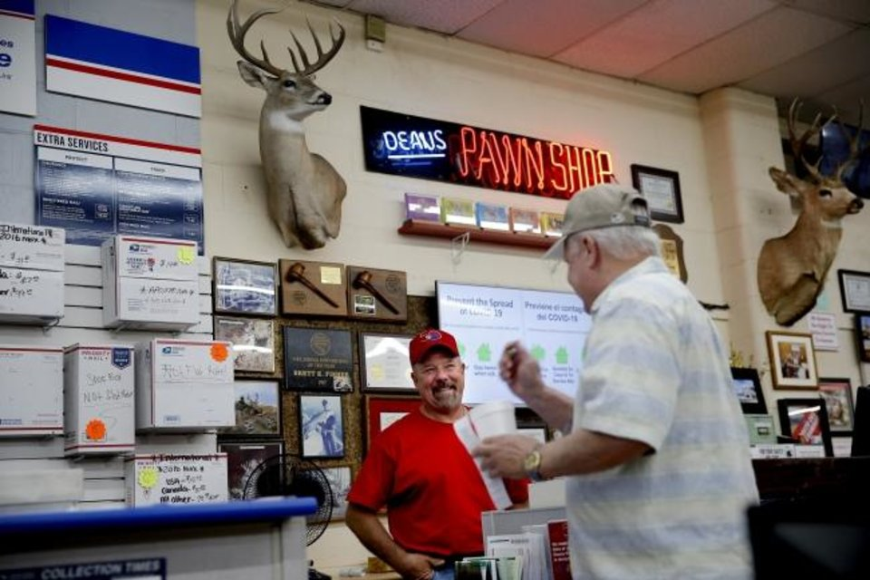 Photo -  Brett Fisher, owner of Dean's Drive-Thru Pawn Shop, talks Wendesday with David Aduddell inside the south Oklahoma City pawn shop. [Bryan Terry/The Oklahoman]