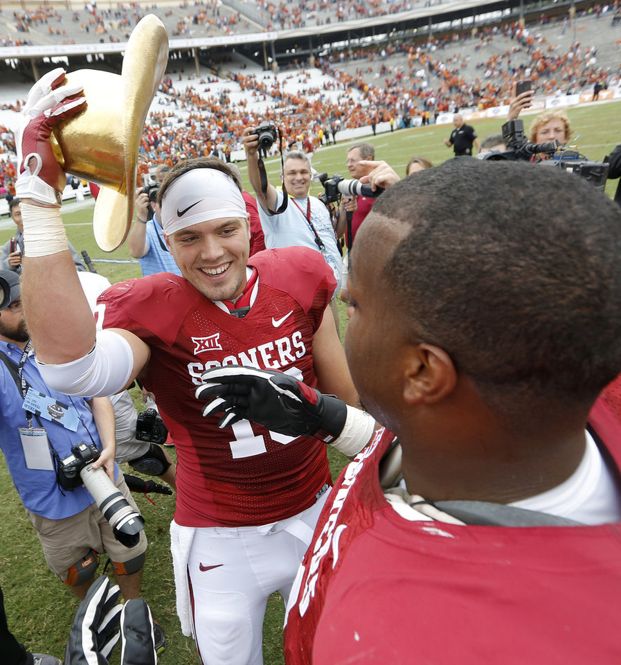 Photo - Oklahoma's Blake Bell (10) celebrates with Adam Shead (74) after the 31-26 win over Texas during the college football game between the University of Oklahoma Sooners (OU) and the University of Texas Longhorns (UT) during the Red River Showdown at the Cotton bowl in Dallas, Texas on Saturday, Oct. 11, 2014. Photo by Chris Landsberger, The Oklahoman