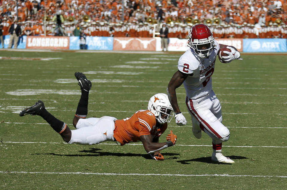 Photo - Oklahoma's CeeDee Lamb (2) gets by Texas defensive back D'Shawn Jamison (5) in the first quarter during the Red River Showdown college football game between the University of Oklahoma Sooners (OU) and the Texas Longhorns (UT) at Cotton Bowl Stadium in Dallas, Saturday, Oct. 12, 2019. [Sarah Phipps/The Oklahoman]