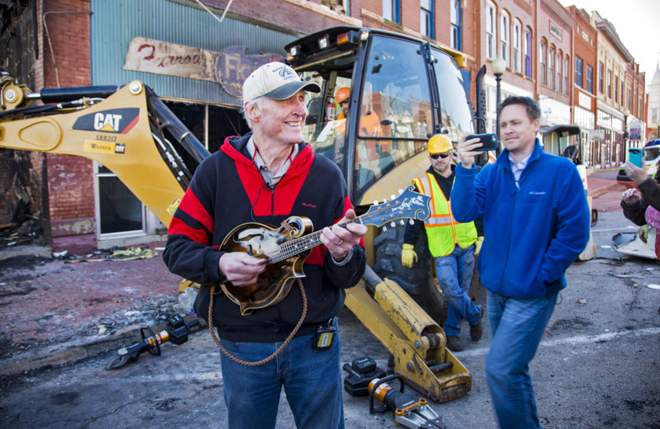 Photo - Fiddle player Byron Berline is all smiles as he plays a tune on his prized 1923 Lloyd Loar Gibson mandolin that was pulled from a safe that was part of the items destroyed by a fire at his fiddle shop in Guthrie, Okla. on Monday, Feb. 25, 2019. The fire on Saturday destroyed two businesses in historic downtown Guthrie.   Photo by Chris Landsberger, The Oklahoman