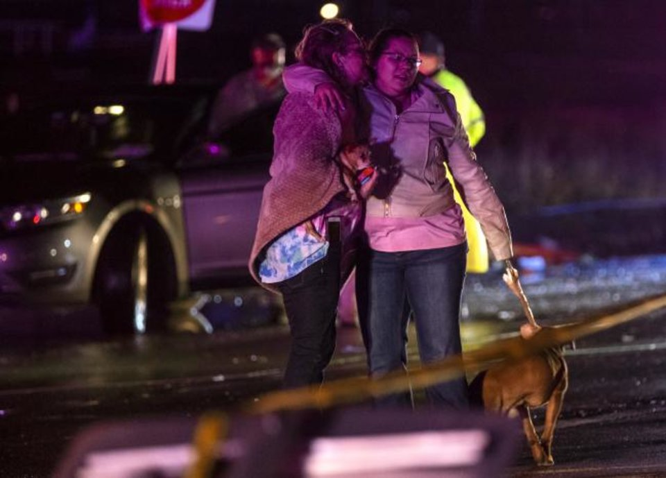 Photo -  People console each other Saturday night in El Reno after a tornado tore across parts of the town, hitting a trailer home park and the American Budget Value Inn. [Chris Landsberger/The Oklahoman]