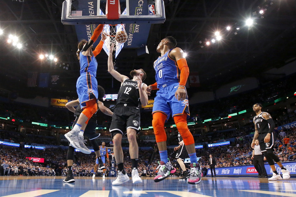Photo - Oklahoma City's Steven Adams (12) dunks beside Brooklyn's Joe Harris (12) on an alley-oop from Russell Westbrook (0) during an NBA basketball game between the Oklahoma City Thunder and the Brooklyn Nets at Chesapeake Energy Arena in Oklahoma City, Wednesday, March 13, 2019. Oklahoma City won 108-96. Photo by Bryan Terry, The Oklahoman
