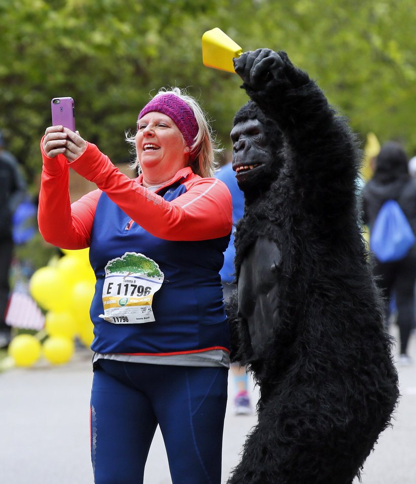 Photo - Tammy Bush takes a selfie with Ben Barenberg, in the gorilla costume, along Gorilla Hill near NW 40 and Shartel Ave. during the the Oklahoma City Memorial Marathon in Oklahoma City, Sunday, April 30, 2017. Photo by Nate Billings, The Oklahoman