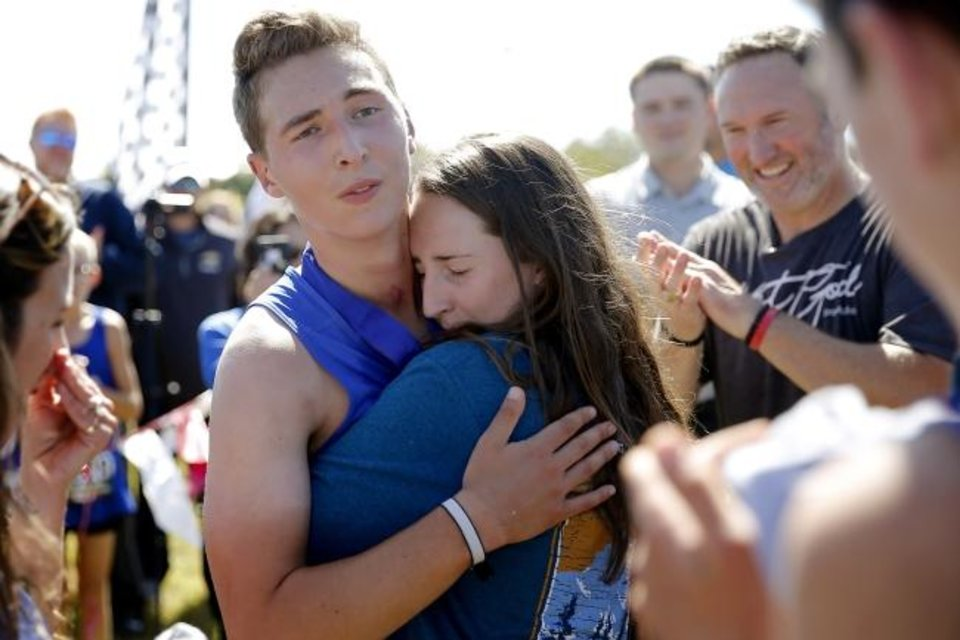 Photo -  Newcastle runner Caleb Freeman, who was injured in a 2017 car crash, hugs his sister Brittany Freeman, 19, after finishing a cross country race at Carl Albert in Midwest City on Tuesday. [Bryan Terry/The Oklahoman]