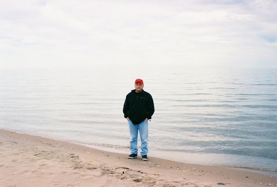 Photo -  Jim stands on the shore of a Wisconsin lake.