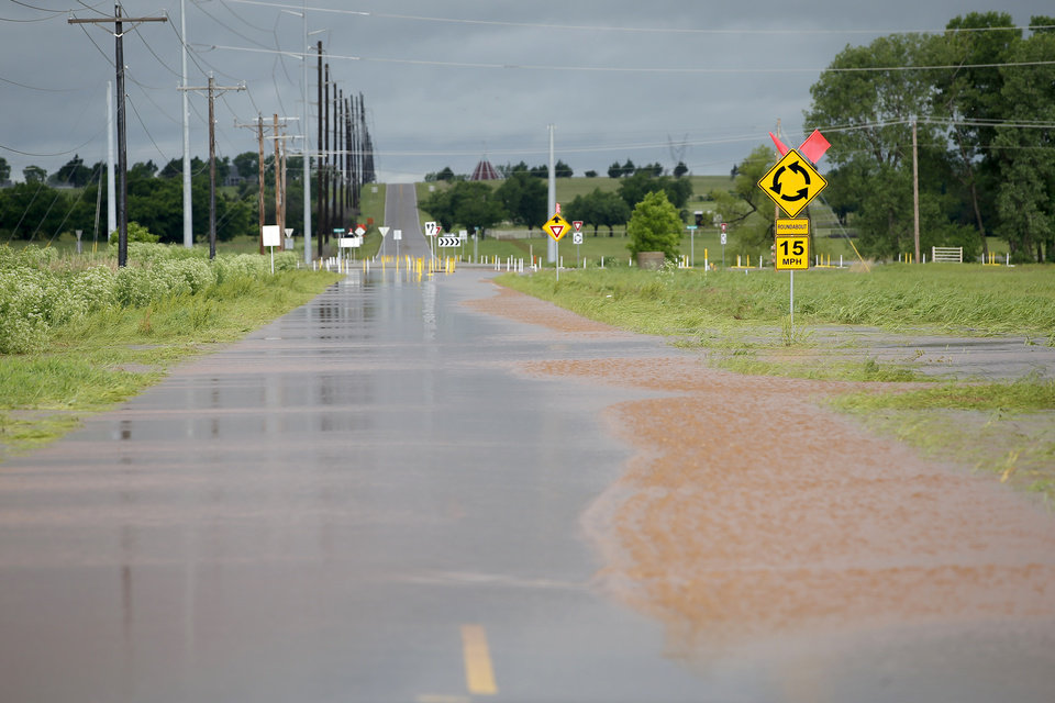Photo - Floodwater flows over NW 178 just west of Portland in Oklahoma City, Tuesday, May 21, 2019. [Bryan Terry/The Oklahoman]