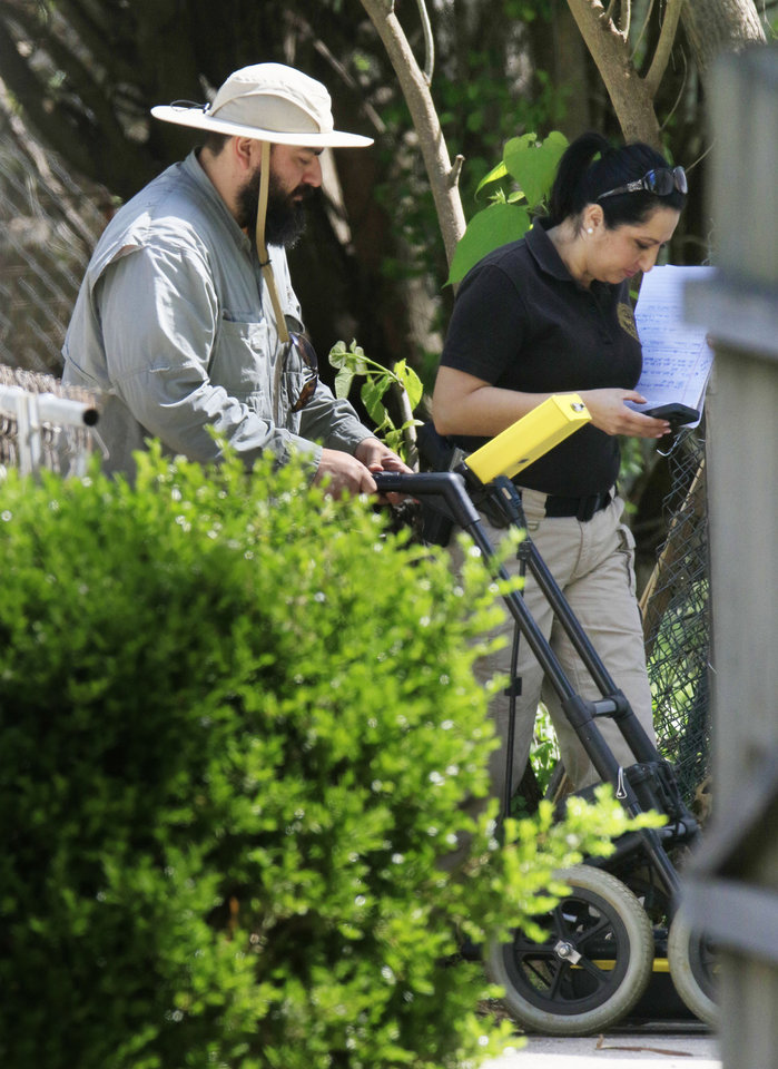 Photo -  Officials with the OSBI use ground-penetrating radar Monday to look for possible human remains behind a house at 504 1/2 N. Oakdale in connection with the homicide case of Carina Saunders. [Photo by Paul Hellstern, The Oklahoman]