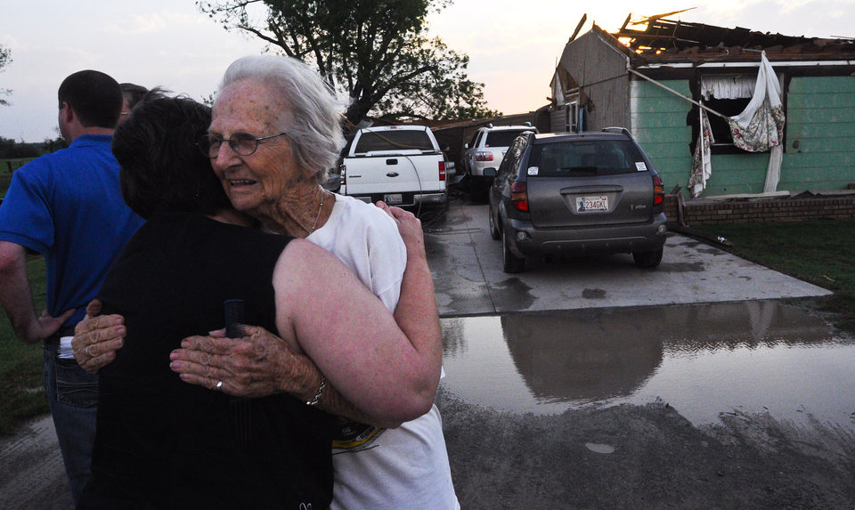 Photo - Ida Clark, 85 of Carney, hugs her friend Lesa Bane after a tornado went through Carney, Okla. on May 19, 2013. Clark's home of 50 years was destroyed by the tornado with Clark and her son inside the house.  KT King/For the Oklahoman