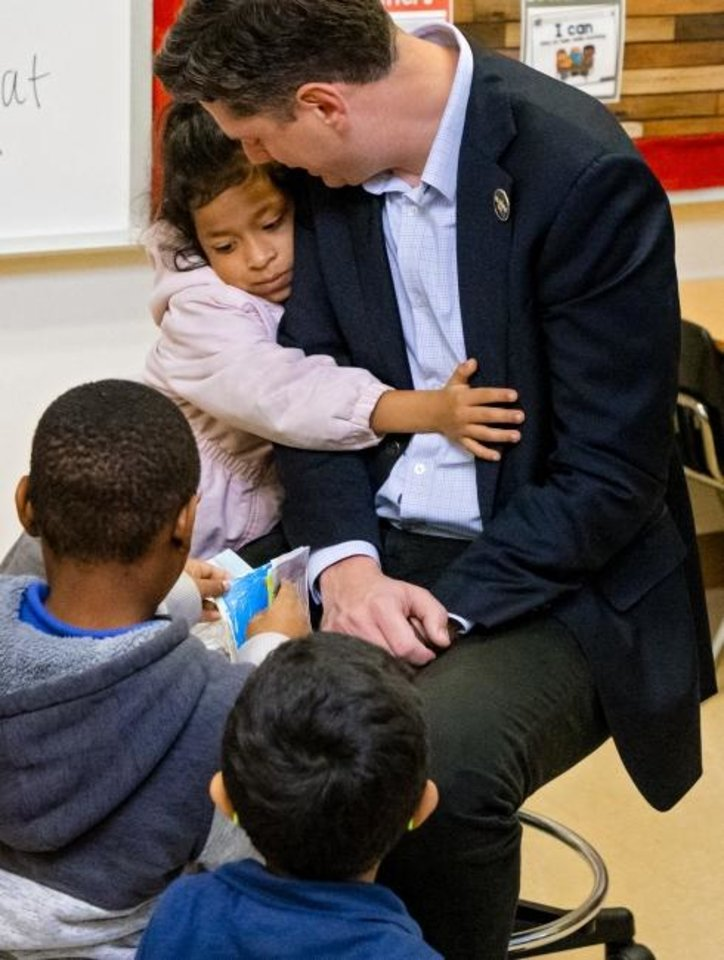 Photo -  Nielisa Luna hugs Mayor David Holt after he read the book 'Goodnight OKC' to Joscilyn Coleman's kindergarten class at Cesar Chavez Elementary in Oklahoma City, Okla Friday, Jan. 10, 2020.    [Chris Landsberger/The Oklahoman]