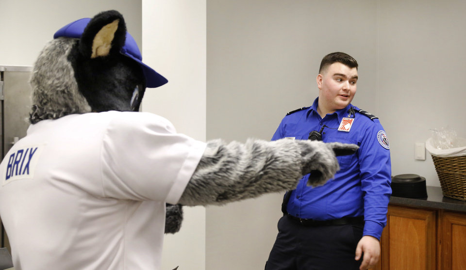 Photo -  Brix, one of two Oklahoma City Dodgers mascots, directs a TSA agent to the food when he arrives for a free meal on Wednesday at Will Rogers World Airport. [Photo by Jim Beckel, The Oklahoman]