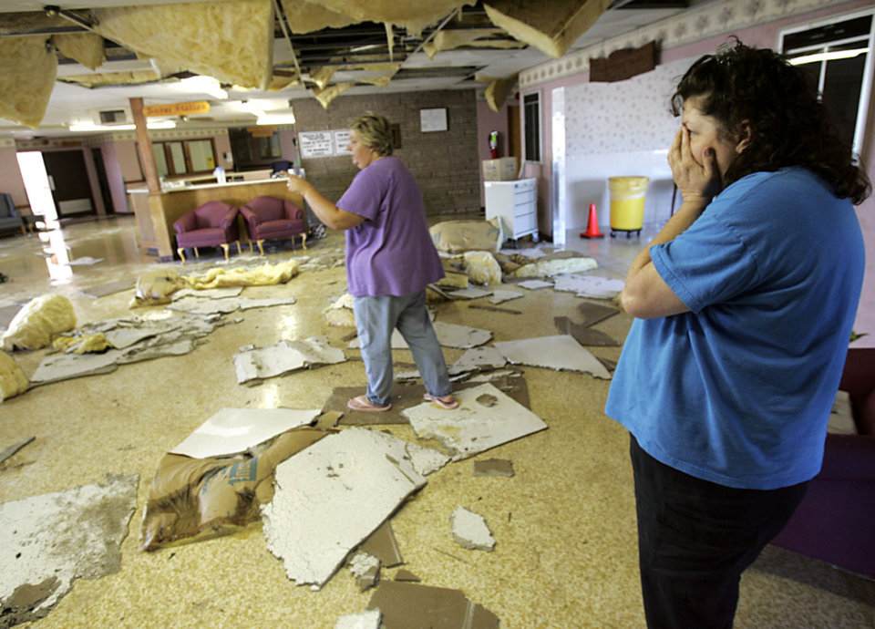 Photo - Employees Anne Chockpoyah (CQ) CHOCKPOYAH (right) reacts as she and Darla Brown look at storm damage at the nursing home in Geary on Sunday, August 19, 2007 following a storm that hit the area early Wednesday morning. By John Clanton, The Oklahoman