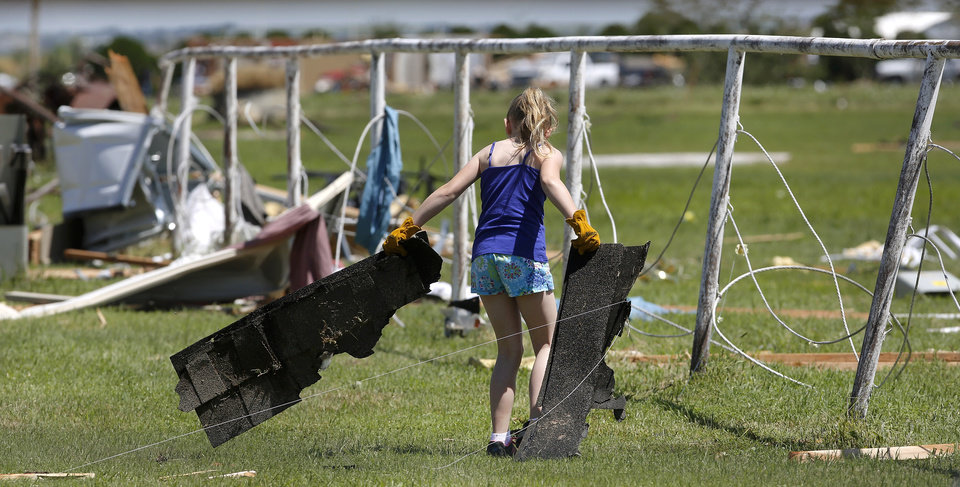 Photo - A girl picks up roofing shingles as she helps clear debris from the yard of  Kay and Bonnie Meritt  on Saturday, June 1, 2013, after the Meritt home at 20545 SW 15 in Union City, was heavily damaged in Friday night's tornado.  Bonnie Meritt said nine homes near her, including hers, were damaged or destroyed in Friday night's tornado. The couple was unharmed. They took shelter inside the Union City fire station before the tornado hit. Photo  by Jim Beckel, The Oklahoman.