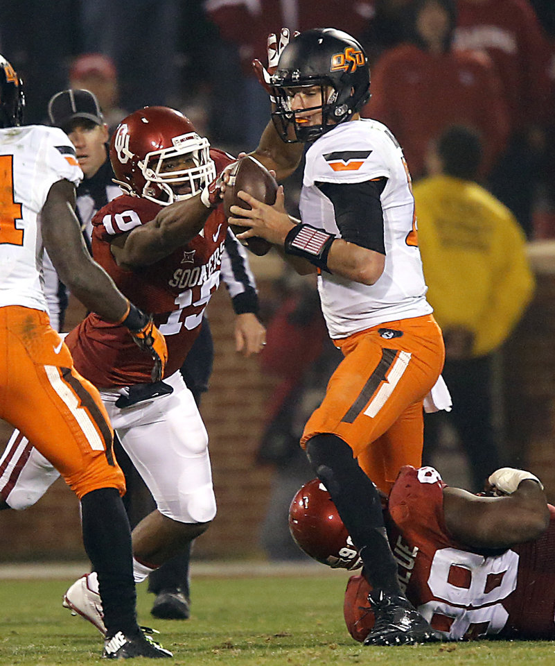 Photo - Oklahoma's Eric Striker (19) and Chuka Ndulue (98) sack Oklahoma State's Mason Rudolph (10) during a Bedlam college football game between the University of Oklahoma Sooners (OU) and the Oklahoma State University Cowboys (OSU) at the Gaylord Family Oklahoma Memorial Stadium in Norman, Okla. on Saturday, Dec. 6, 2014. Photo by Chris Landsberger, The Oklahoman