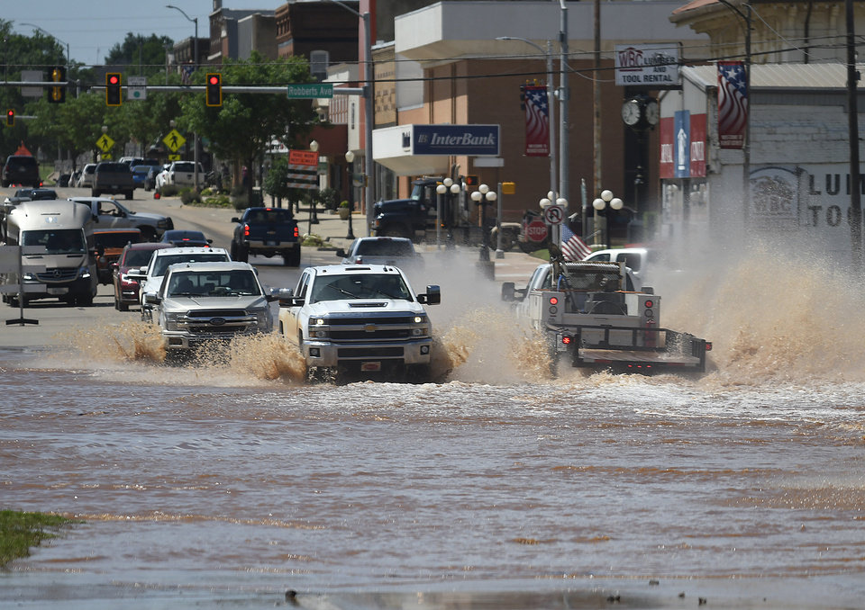 Photo - Traffic drives through flood water across U.S. 81 in downtown Kingfisher, Okla., Tuesday, May 21, 2019 prior to law enforcement diverting traffic. (Billy Hefton / Enid News & Eagle via AP)