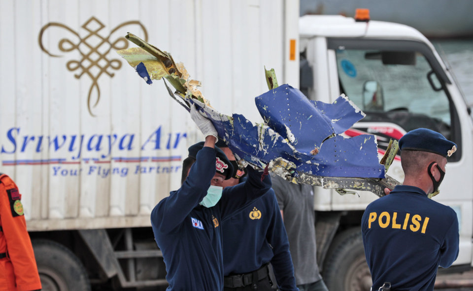 Photo -  Police officers carry a part of aircraft recovered from Java Sea where a Sriwijaya Air passenger jet crashed, at Tanjung Priok Port in Jakarta, Indonesia, Monday, Jan. 11, 2021. The search for the black boxes of a crashed Sriwijaya Air jet intensified Monday to boost the investigation into what caused the plane carrying dozens of people to nosedive at high velocity into the Java Sea. (AP Photo/Dita Alangkara)