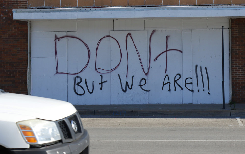 Photo - Graffiti on buildings across the street from the Walgreens at NW 23rd and Classen Blvd. Damage from Saturday night protest in downtown Oklahoma City, Sunday, May 31, 2020. [Doug Hoke/The Oklahoman]