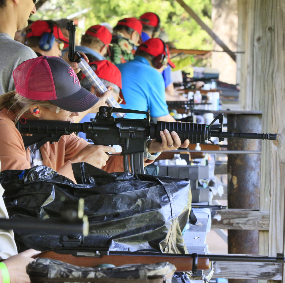 Photo -  Women line up on the Oklahoma City Gun Club's .22 rifle range to shoot different styles of rifles during the annual women's fun shoot on Sept. 10. The annual event is the largest instructional shoot for women in the country. (Photo by Paul Hellstern, The Oklahoman)