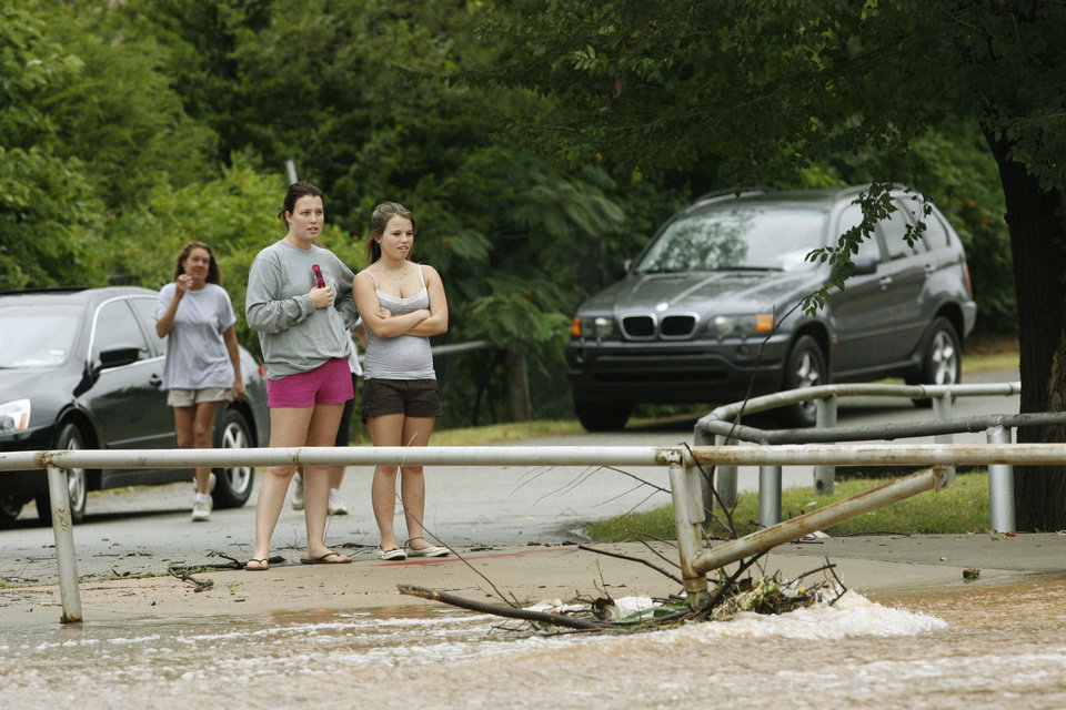 Photo - People gather near the South Shore Drive spillway through the Silver Lake addition to watch the water Sunday Aug 19, 2007. By James Plumlee, The Oklahoman.
