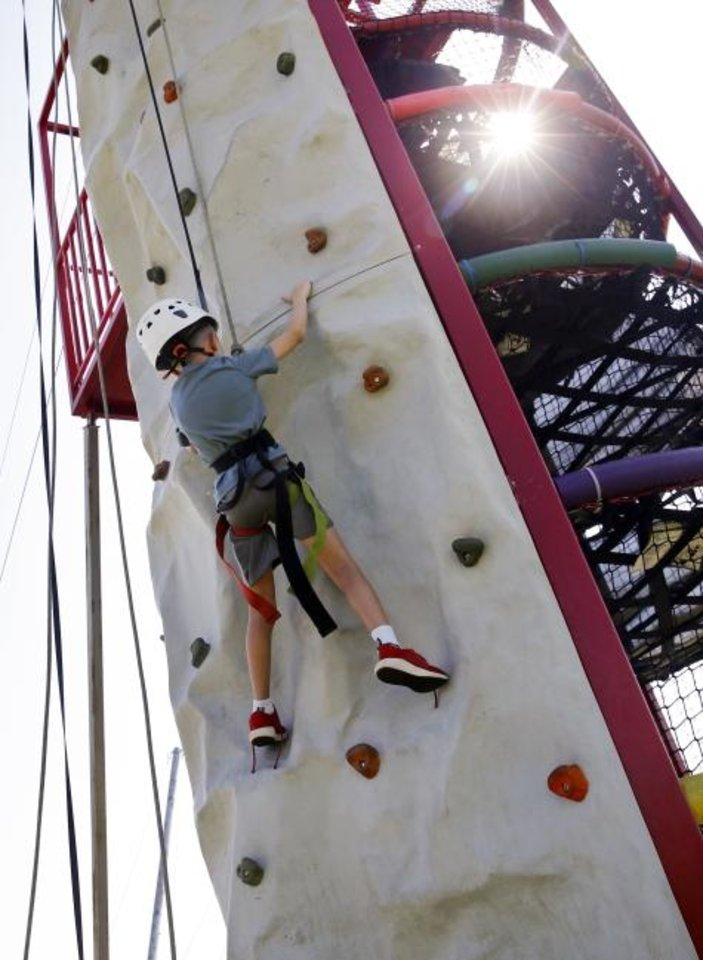 Photo -  Turner Smith, 7, pauses while ascending a climbing wall Wednesday. [Nate Billings/The Oklahoman]