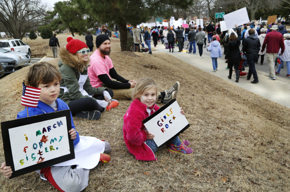 Photo - Judah Alvaro, 9, left, holds a sign he made to show his support for his younger sister, Ruthie, 6, as they watch marchers pass on Lincoln Blvd. The children attended the rally with their parents, John Jay and Corrie Alvaro, Oklahoma City. A crowd estimated by organizers to be as many as 7,000 people came to the state Capitol in Oklahoma City Saturday, Jan. 21, 2017, to rally, using their voices and signs to express displeasure with the nation's new administration as part of a larger network of marches taking place across the country following Donald Trump's inauguration.   The Women's March on Oklahoma included a walk along Lincoln Blvd., with the Capitol as a backdrop, and a rally on the Capitol's south plaza that featured nearly a dozen speakers.  Photo by Jim Beckel, The Oklahoman