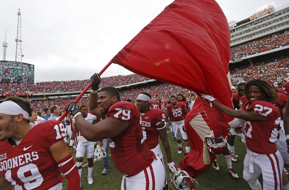 Photo - Oklahoma's Daryl Williams (79) carries on OU flag after the Red River Showdown college football game between the University of Oklahoma Sooners (OU) and the University of Texas Longhorns (UT) at the Cotton Bowl in Dallas on Saturday, Oct. 11, 2014. 
