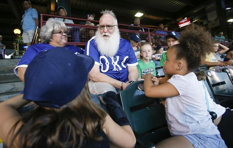 Photo - Ron Herendeen, known as Santa Ron, talks with Brayleigh Taylor, 8, front left, and Gabriella Piccione, 7, front right, next to Tenley Richmond, 8, second from right, Coley Richmond, 8, right, and his wife Elaine Herendeen, left, as he and his Team Santa kids attend an Oklahoma City Dodgers baseball game at the Chickasaw Bricktown Ballpark in Oklahoma City, Friday, Aug. 24, 2018. Team Santa is a program to promote health and fitness in youngsters that Santa Ron started after he was diagnosed with Type 2 diabetes. Photo by Nate Billings, The Oklahoman