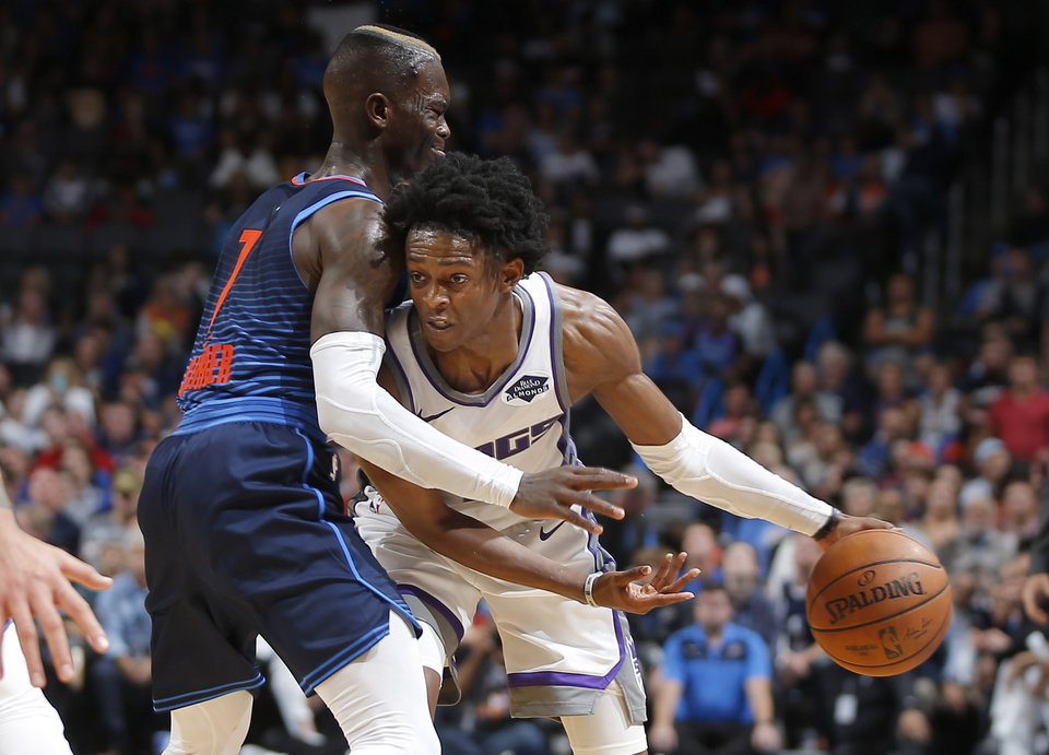 Photo - Sacramento's De'Aaron Fox (5) tries to get past Oklahoma City's Dennis Schroder (17) during an NBA basketball game between the Oklahoma City Thunder and the Sacramento Kings at Chesapeake Energy Arena in Oklahoma City, Sunday, Oct. 21, 2018. Photo by Bryan Terry, The Oklahoman