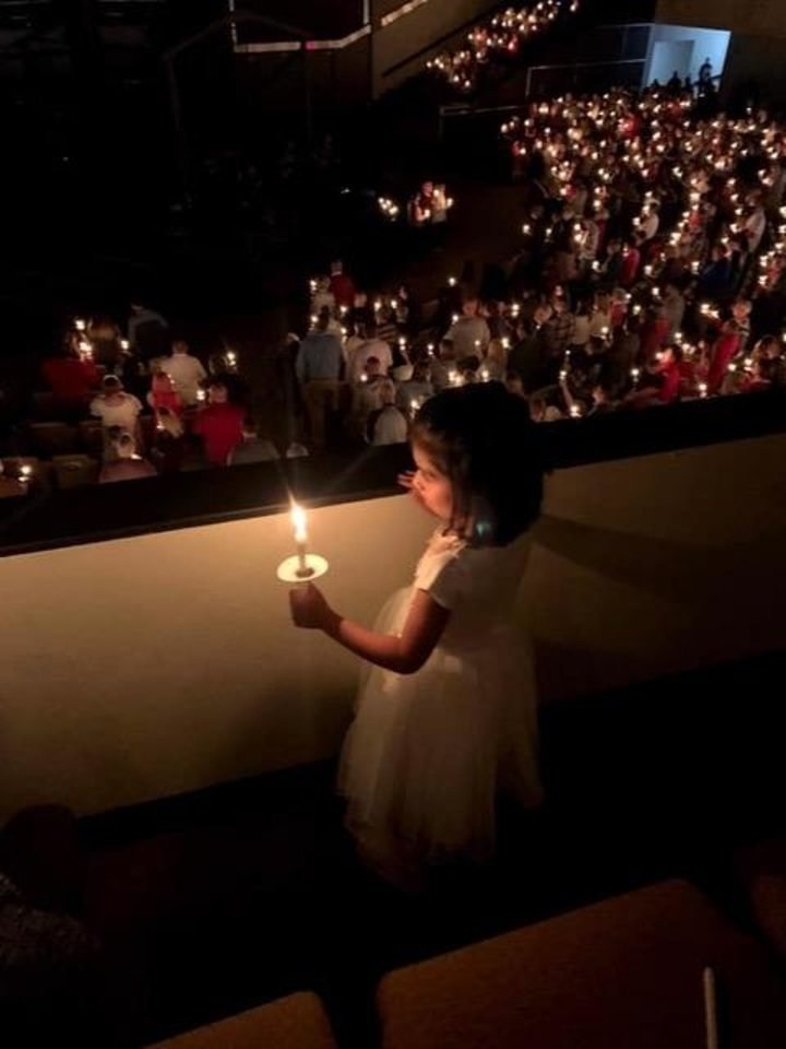 Photo -  A child holds a lighted candle during a Candlelight Service held on Christmas Eve in a previous year at Council Road Baptist Church in Bethany. [Photo provided]