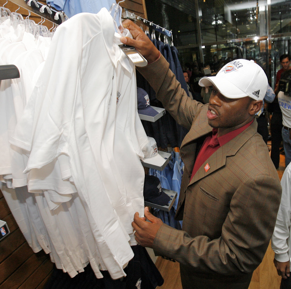 Photo - OKC Thunder player Desmond Mason picks out shirts in the team store after the unveiling of the Oklahoma City Thunder NBA team name at Leadership Square in downtown Oklahoma City, Wednesday, September 3, 2008. NATE BILLINGS, THE OKLAHOMAN