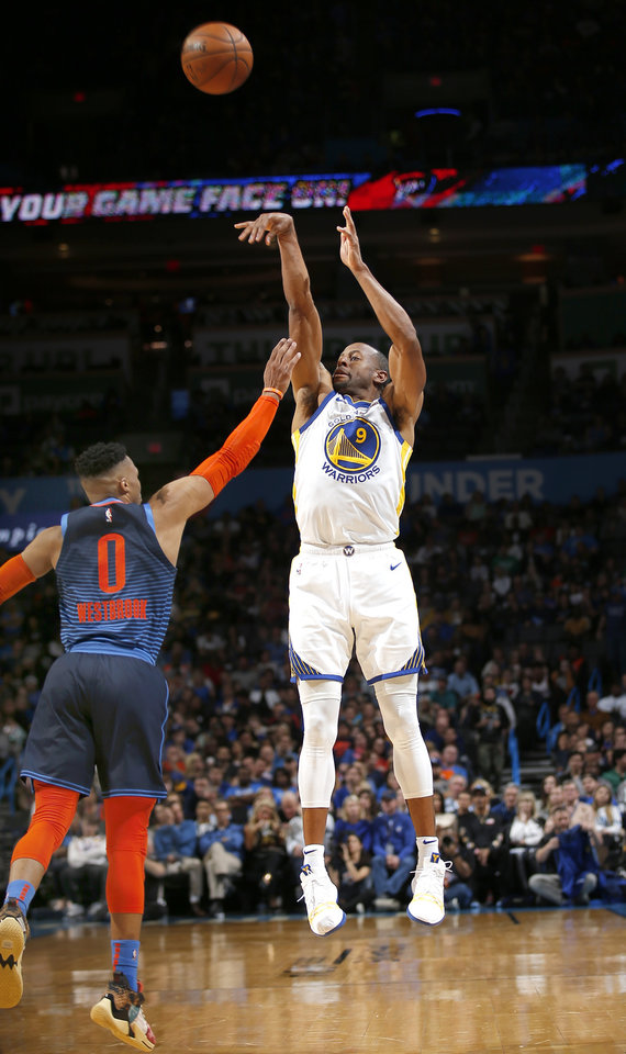 Photo - Golden State's Andre Iguodala (9) shoots over Oklahoma City's Russell Westbrook (0) during the NBA basketball game between the Oklahoma City Thunder and the Golden State Warriors at Chesapeake Energy Arena,  Saturday, March 16, 2019. Photo by Sarah Phipps, The Oklahoman
