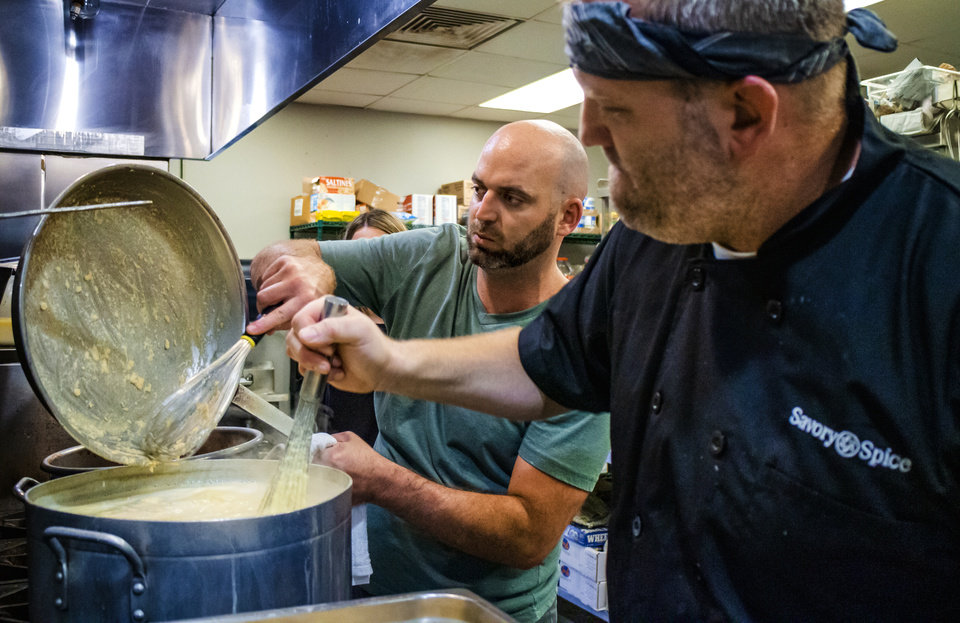 Photo - Ryan Goodman and Able Blakley, from left, prepare food as 84 Hospitality works the kitchen of The Westtown day shelter at the Homeless Alliance to make lunch for the shelter's clients in Oklahoma City, Okla. on Monday, May 6, 2019.    [Chris Landsberger/The Oklahoman]