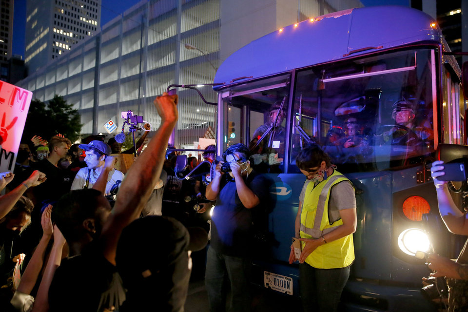 Photo - Protesters block a bus filled with Oklahoma National Guard members after a President Donald Trump rally at the BOK Center in Tulsa, Okla., Saturday, June 20, 2020. [Bryan Terry/The Oklahoman]