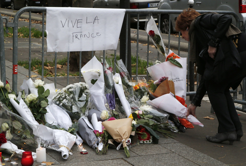 Photo - A woman lays flowers outside the Bataclan theater in Paris, Saturday, Nov. 14, 2015. rench President Francois Hollande vowed to attack the Islamic State group without mercy as the jihadist group claimed responsibility Saturday for orchestrating the deadliest attacks on France since World War II. Poster reads Long Live France. (AP Photo/Michel Euler)
