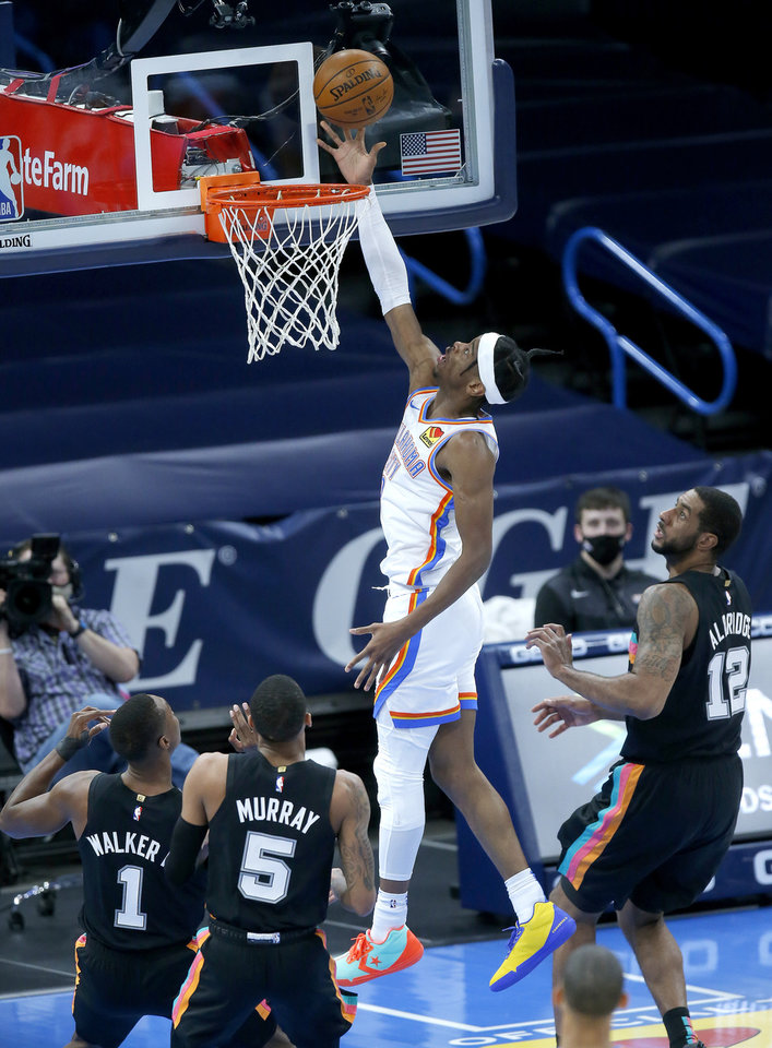 Photo - Oklahoma City's Shai Gilgeous-Alexander (2) goes up for a lay up in between San Antonio's Lonnie Walker IV (1), Dejounte Murray (5) and LaMarcus Aldridge (12) in the second quarter of the NBA basketball game between the Oklahoma City Thunder and the San San Antonio Spurs at the Chesapeake Energy Arena, Wednesday, Feb. 24, 2021. [Sarah Phipps/The Oklahoman]